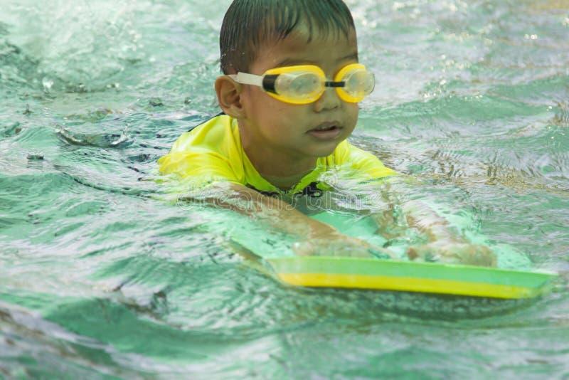 Pojkeövningssimning simning för aktivitetsbarnpöl arkivfoton