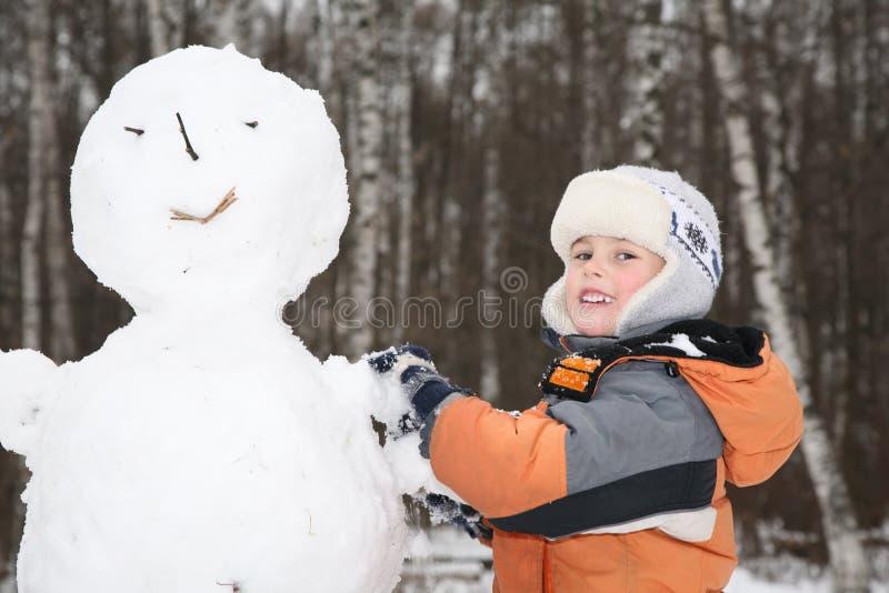 pojke 2 gör snowmanen arkivfoto
