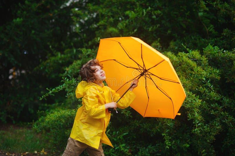 Pojke av 8-9 år med ett gult paraply mot storartade gräsplaner arkivbild