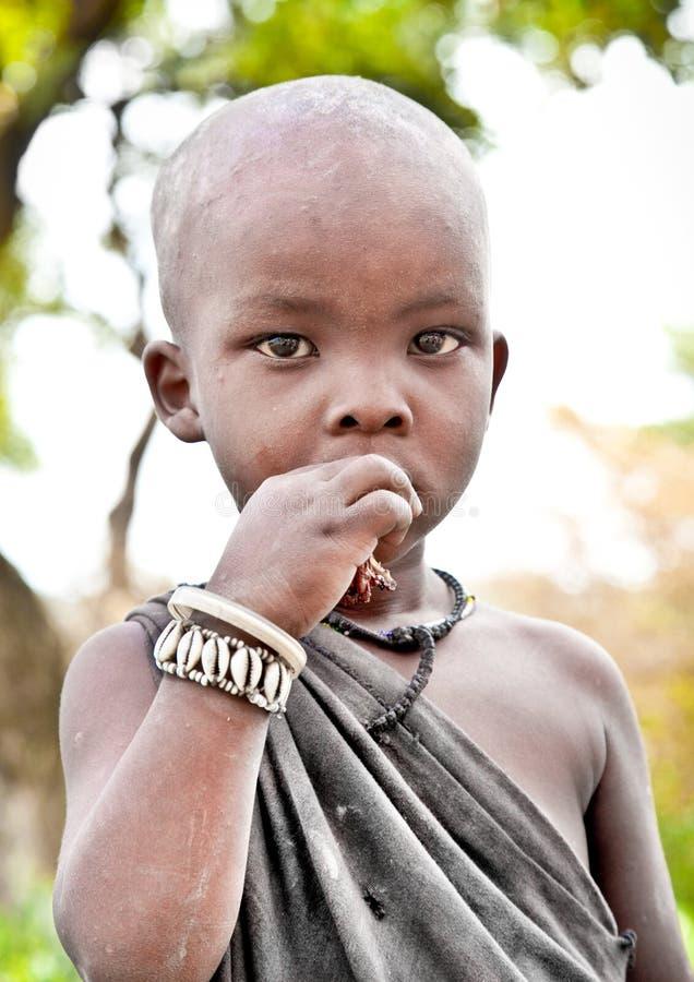 Pojke av Masaistammen som ser till kameran i Tanzania arkivbilder
