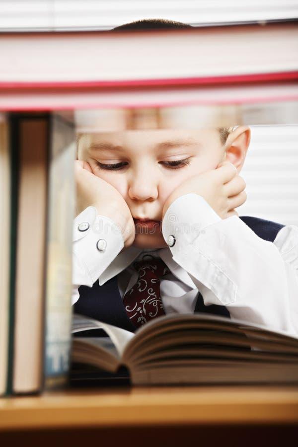 Pojke bak att läsa för böcker fotografering för bildbyråer