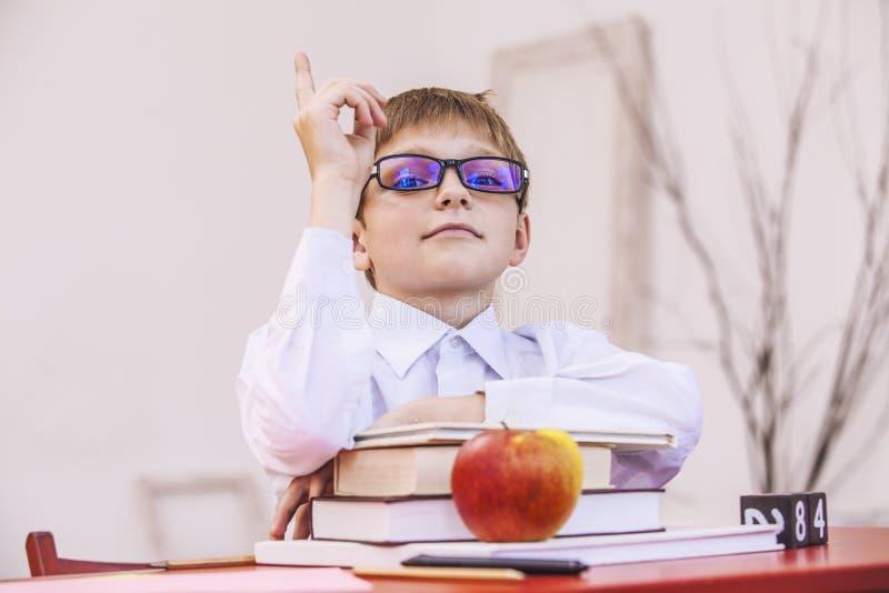 Pojke barn, på skolan, på ett skolaskrivbord med böcker i glassen royaltyfri foto