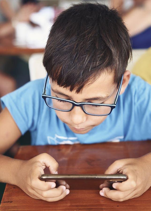 Pojke för gröna ögon med exponeringsglas som spelar med hans telefon royaltyfria foton