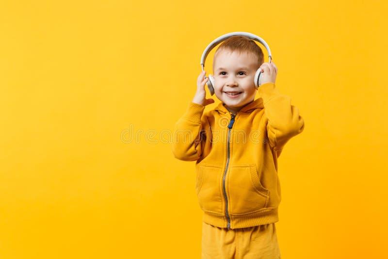 Pojke för liten unge 3-4 år gammal bärande gul kläder i hörlurar som isoleras på orange väggbakgrund, barnstudio royaltyfri foto