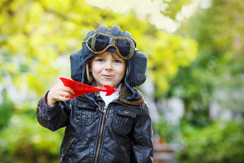 Pojke för liten unge i den pilot- hjälmen som spelar med leksakflygplanet royaltyfri fotografi