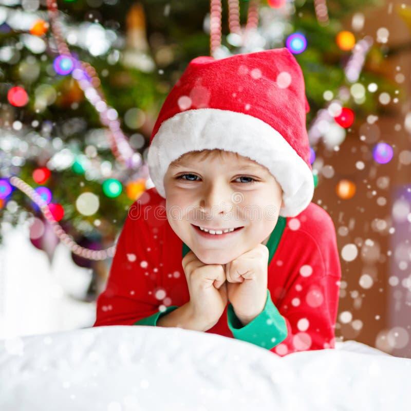 Pojke för liten unge i den santa hatten med julgranen och ljus på bakgrund royaltyfria foton