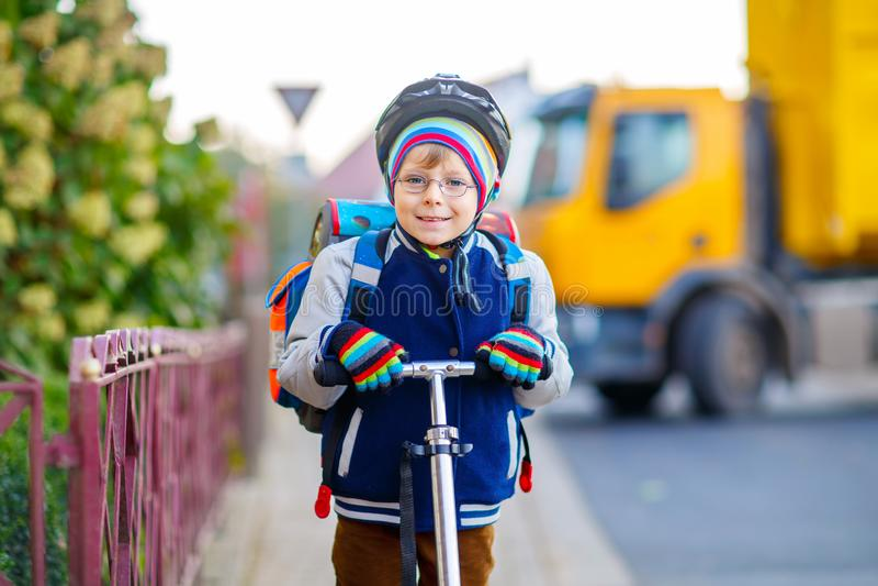 Pojke för liten unge i hjälmridning med hans sparkcykel i staden royaltyfri bild