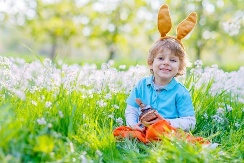 Pojke för liten unge med öron och muffin för påskkanin fotografering för bildbyråer