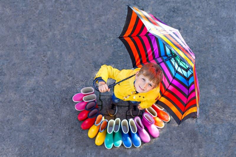Pojke för liten unge och grupp av färgrika regnkängor Blont barnanseende under paraplyet Närbild av skolbarnet och arkivfoto