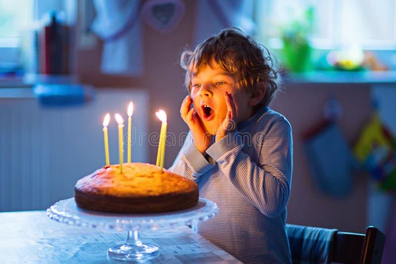 Pojke för liten unge som firar hans födelsedag och blåser stearinljus på kakan arkivfoton