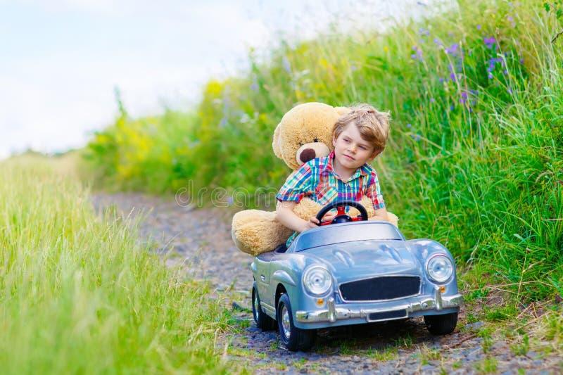 Pojke för liten unge som kör den stora leksakbilen med en björn, utomhus royaltyfri bild