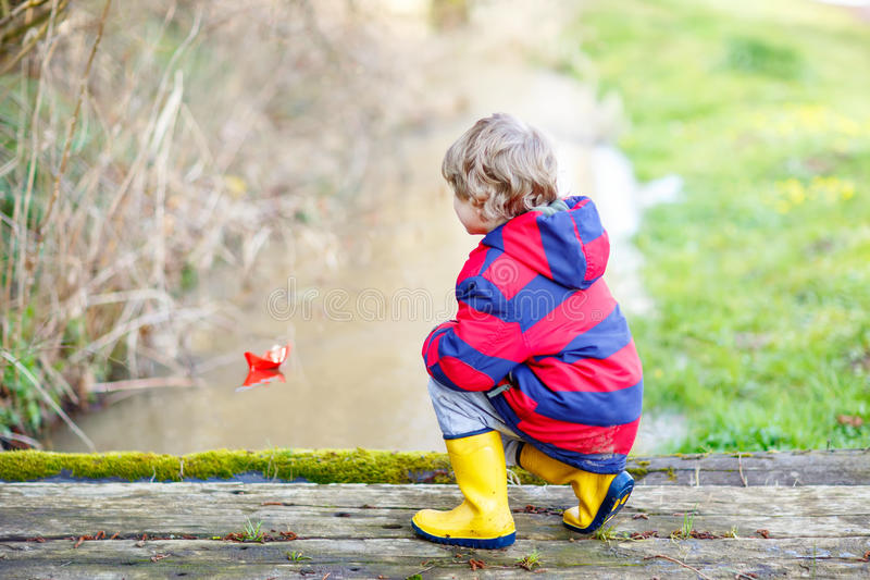 Pojke för liten unge som spelar med det pappers- skeppet vid liten vik arkivbilder