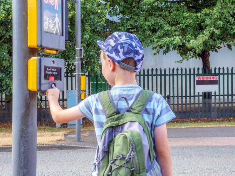 Pojke för litet barn för dagsikt med den trängande fot- signalknappen för ryggsäck som korsar den brittiska vägen arkivbilder