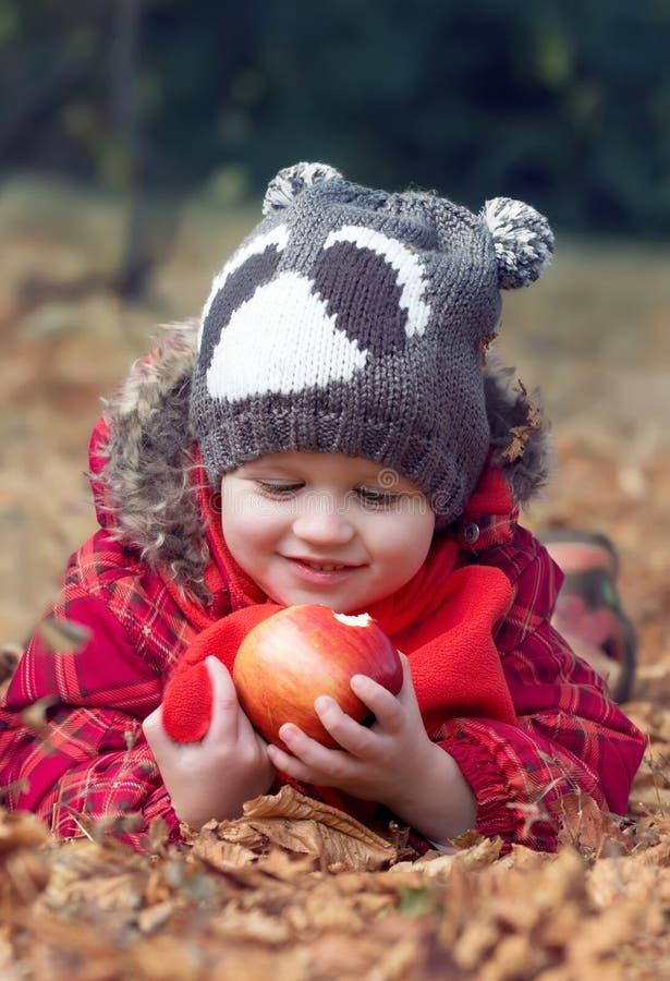 Pojke för litet barn med för äpple höst utomhus arkivfoto