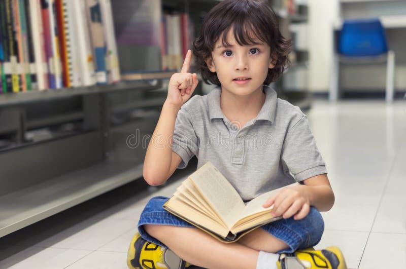 Pojke för litet barn som läser en bok och ett finger som pekar upp arkivbilder