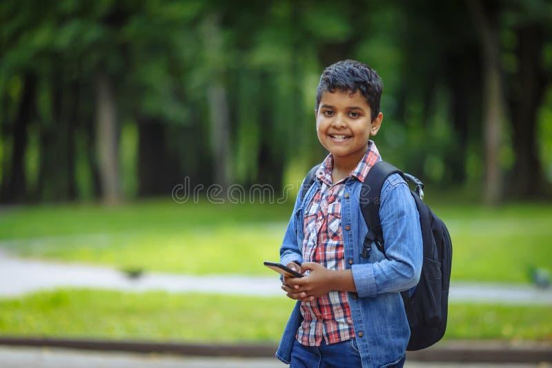 Pojke för skola för utomhus- amerikan för stående afro lycklig med böcker och ryggsäcken Ung studentb?rjan av grupp efter semeste arkivfoton