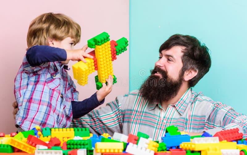 Pojke f?r faderledarevisning hur v?x in i lyckad man Farsa och unge att bygga plast- kvarter Barnav?rd och uppfostran royaltyfri foto