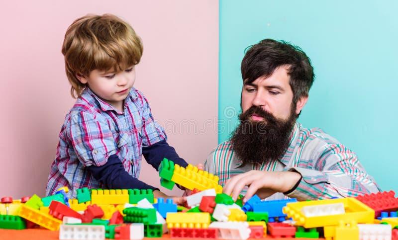 Pojke f?r faderledarevisning hur v?x in i lyckad man Farsa och unge att bygga plast- kvarter Barnav?rd och uppfostran royaltyfria foton