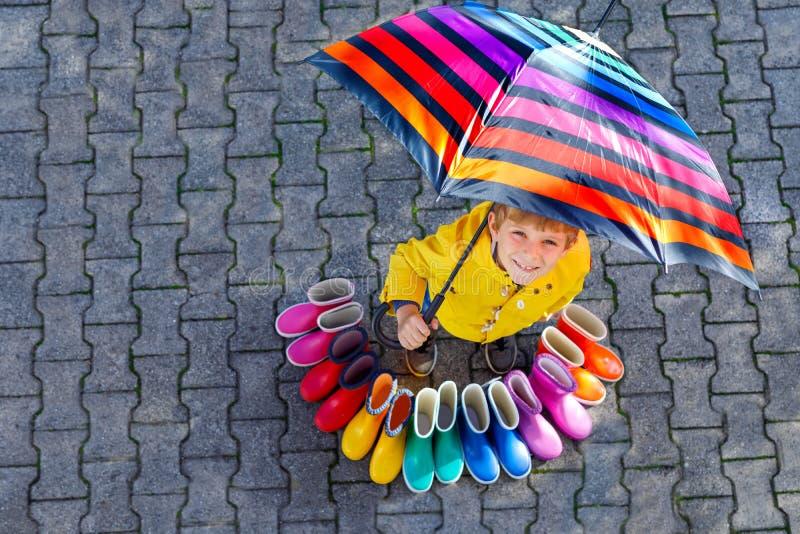 Pojke f?r liten unge och grupp av f?rgrika regnk?ngor Blont barnanseende under paraplyet N?rbild av skolbarnet och arkivfoto