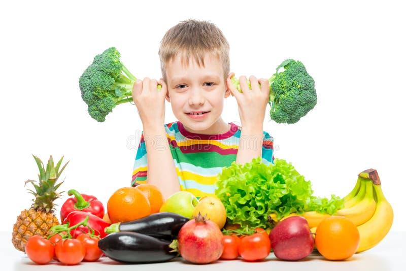 Pojke 10 gamla år med broccoli och en grupp av grönsaker och frukter som poserar i studion som isoleras på vit fotografering för bildbyråer