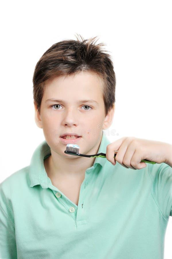 Pojke 12 gamla som år borstar hans tänder royaltyfri foto