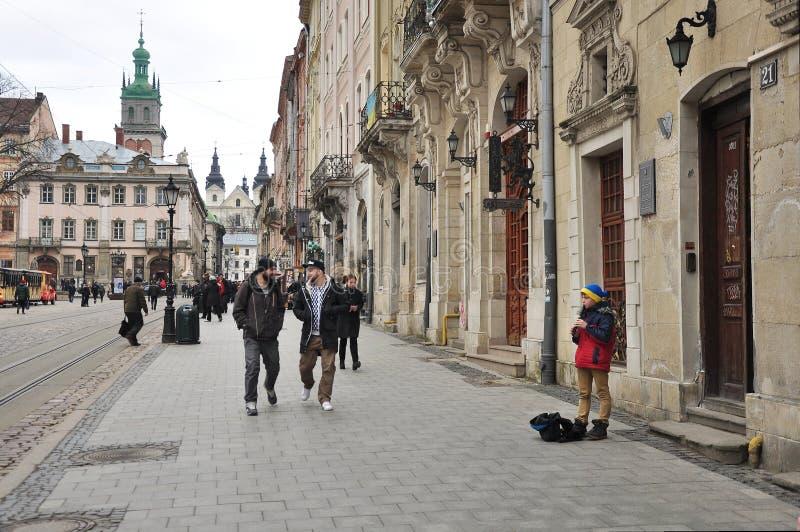 Pojke - gatamusiker, förbipasserande, medeltida arkitektur av Lviv arkivfoto
