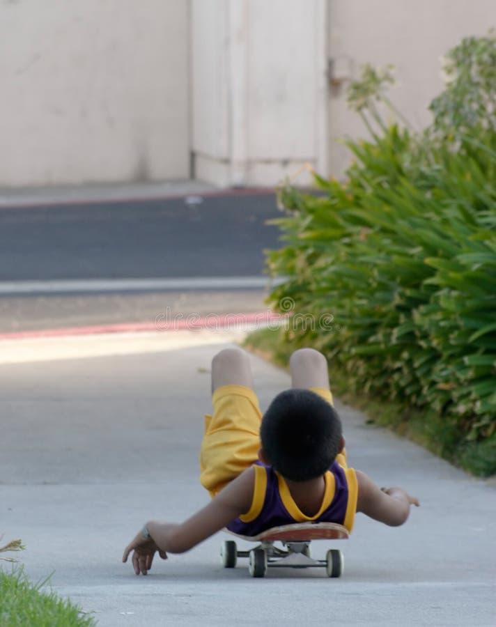 pojke hans läggande skateboard royaltyfri fotografi