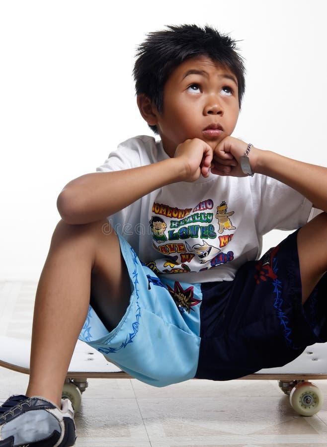 pojke hans seende sittande skateboard upp arkivbilder
