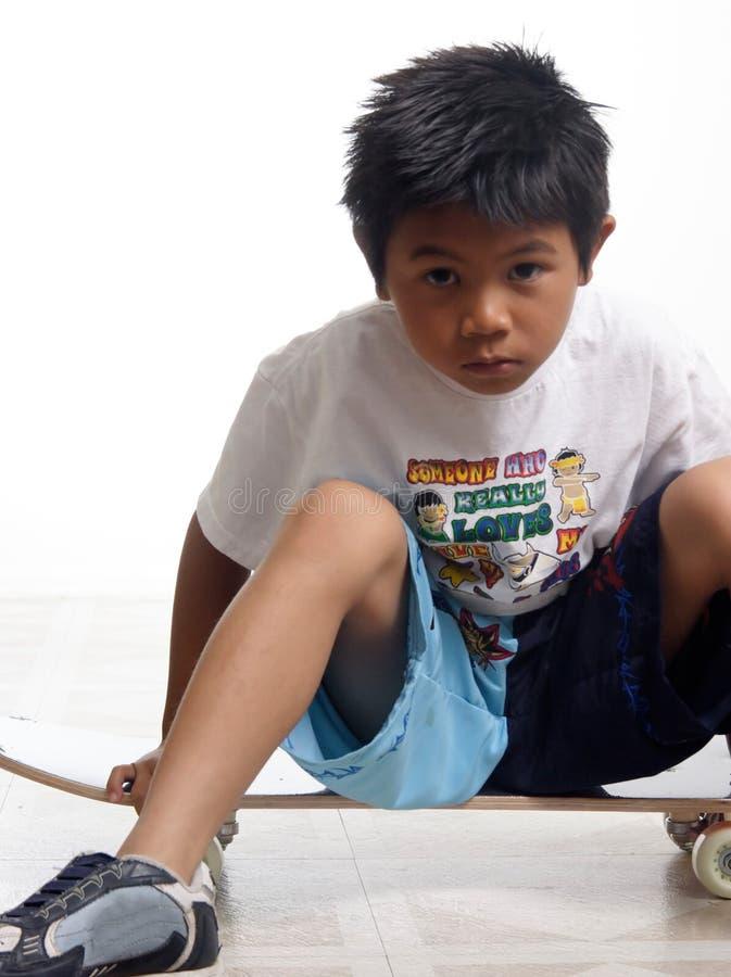 pojke hans sittande skateboard arkivfoton