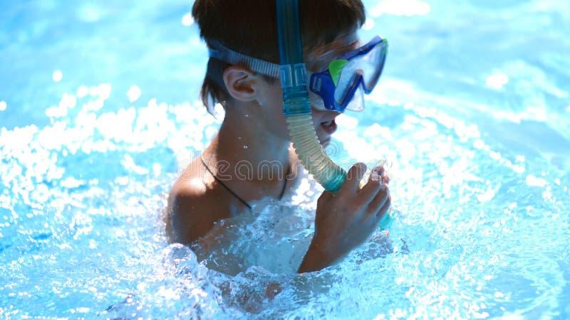 Pojke, i att simma maskeringen i pölen royaltyfri bild