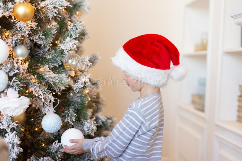 Pojke i den santa hatten som dekorerar julträdet med bollar julen dekorerar nya home idéer för garnering till isolerat nytt vitt  royaltyfri foto