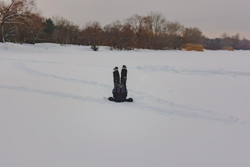Pojke i den uppochnervända snön royaltyfri bild