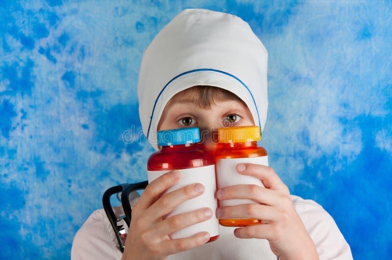Pojke i doktorsdräkten som ut ser preventivpillerflaskor fotografering för bildbyråer