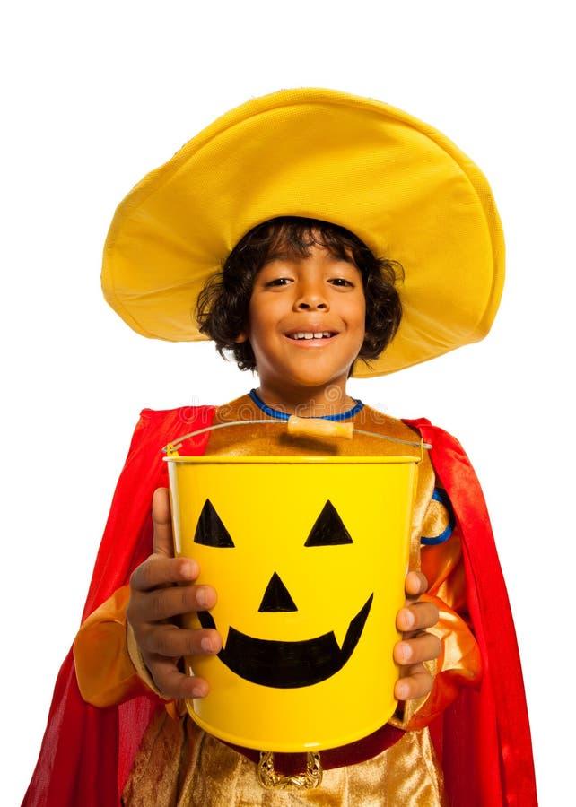 Pojke i dräkt med den spöklika godishinken för allhelgonaafton royaltyfri foto