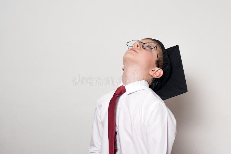 Pojke i en fyrkantig akademisk hatt- och exponeringsglaslookong upp skola f?r copyspace f?r begrepp f?r svarta b?cker f?r bakgrun arkivfoto