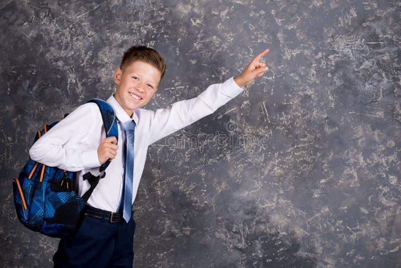 Pojke i en vit skjorta och band med en ryggsäck royaltyfri bild