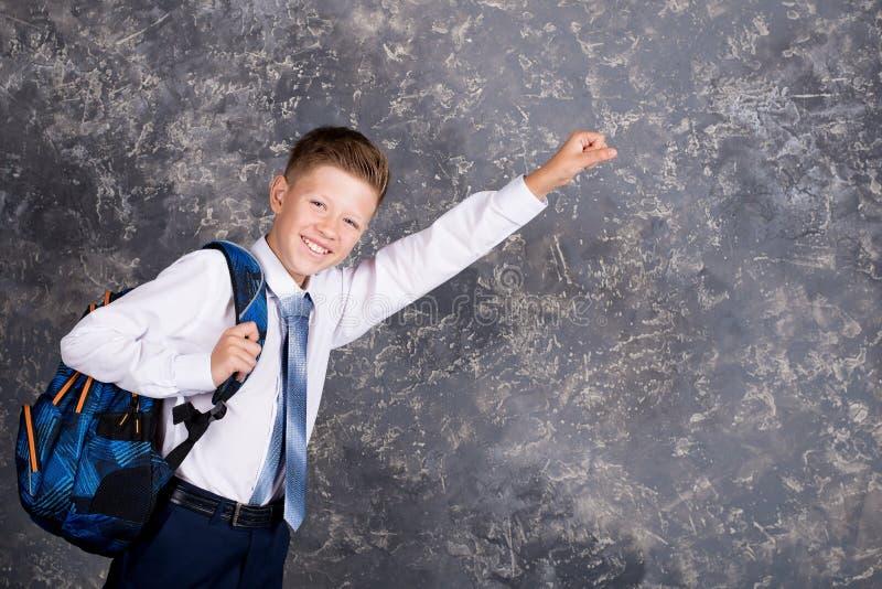 Pojke i en vit skjorta och band med en ryggsäck arkivfoton