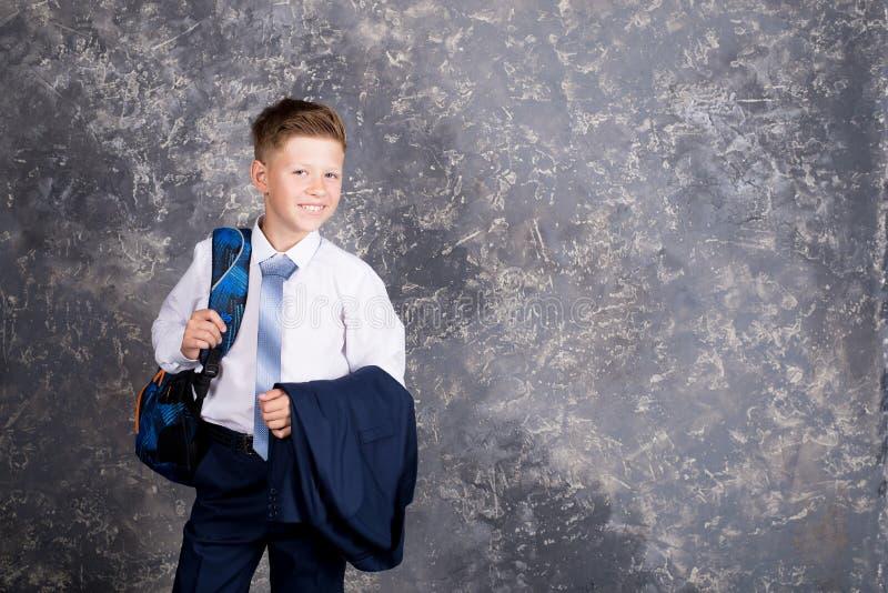Pojke i en vit skjorta och band med en ryggsäck arkivbilder