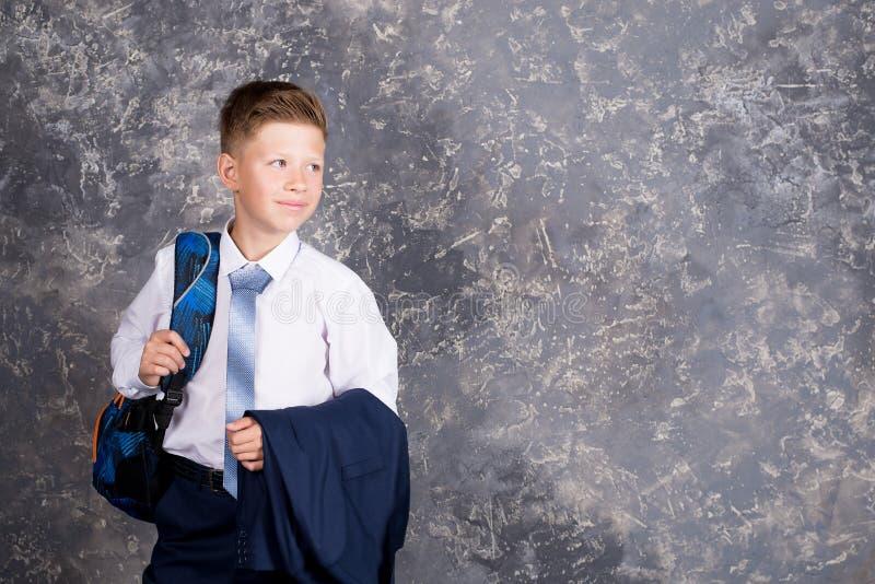 Pojke i en vit skjorta och band med en ryggsäck royaltyfria foton