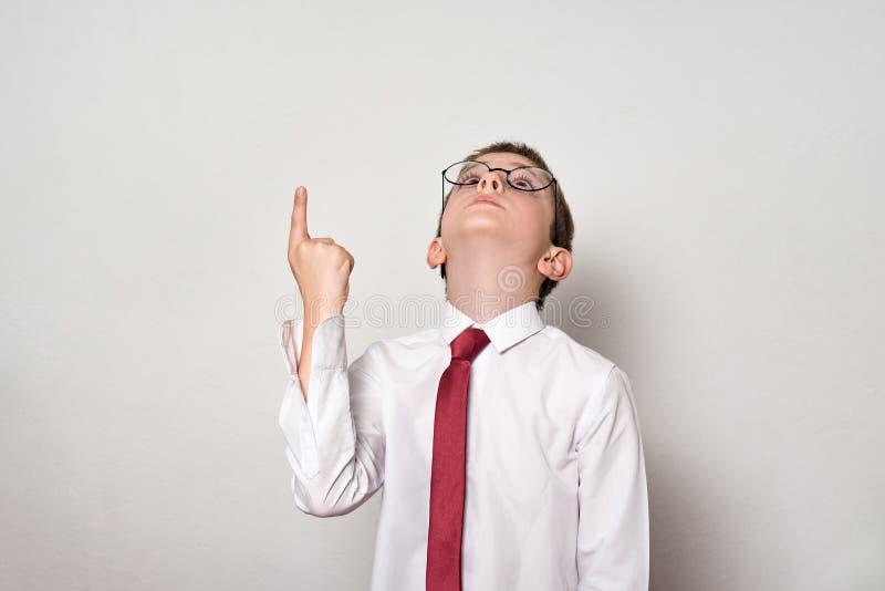 Pojke i en vit skjorta och exponeringsglaspunkter hans finger upp skola f?r copyspace f?r begrepp f?r svarta b?cker f?r bakgrund  royaltyfri fotografi