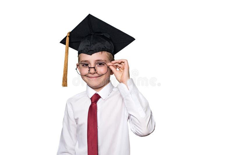 Pojke i ett fyrkantigt akademiskt lock och en vit skjorta som korrigerar exponeringsglas skola f?r copyspace f?r begrepp f?r svar royaltyfri bild