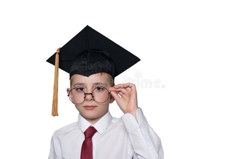 Pojke i ett fyrkantigt akademiskt lock och en vit skjorta som korrigerar exponeringsglas skola f?r copyspace f?r begrepp f?r svar arkivfoton