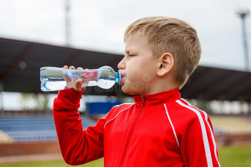Pojke i ett rött enhetligt dricksvatten från en liten flaska på en sportstadion arkivfoton