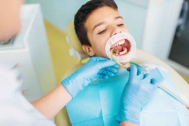 Pojke i ett tand- kabinett, kariesborttagning arkivfoto