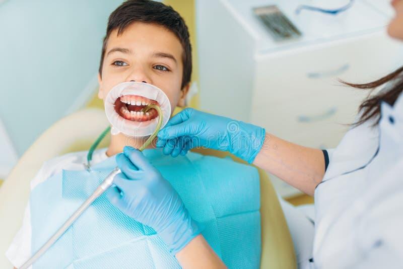 Pojke i ett tand- kabinett, kariesborttagningstillvägagångssätt arkivbilder