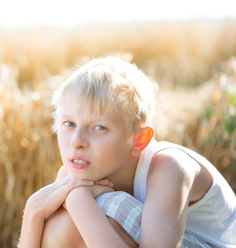 Pojke i ett vetefält arkivfoto