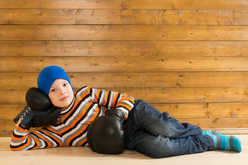 Pojke i gamla handskar för att boxas som vilar på trägolvet fotografering för bildbyråer