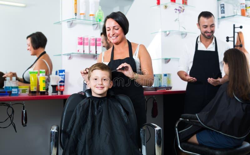 Pojke i grundskolaåldern som får frisyren av frisören arkivfoto