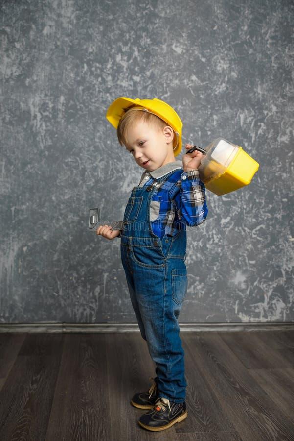 Pojke i hård hatt med konstruktionslinjen och ask av hjälpmedel arkivbilder