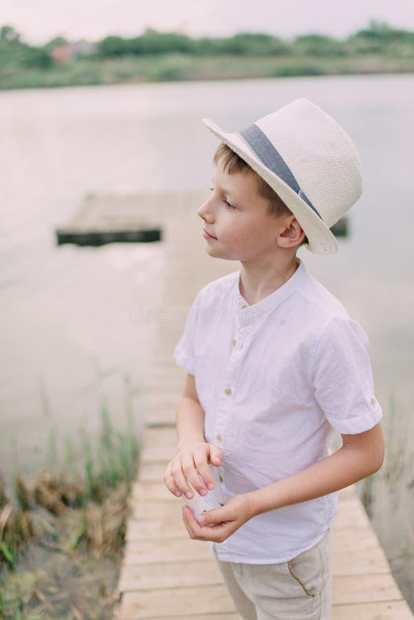 Pojke i hatt nära floden royaltyfria bilder